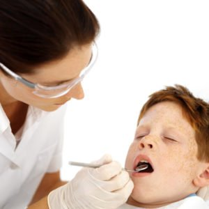 Dentist Examining Little Boys Teeth --- Image by © Royalty-Free/Corbis